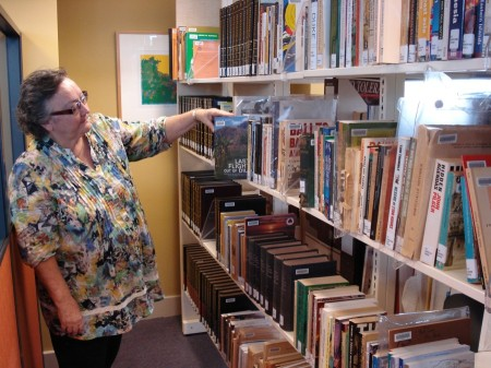 CDU Library Director Ruth Quinn with some of the catalogued monographs in the Sherlock Collection. [CHART photo]