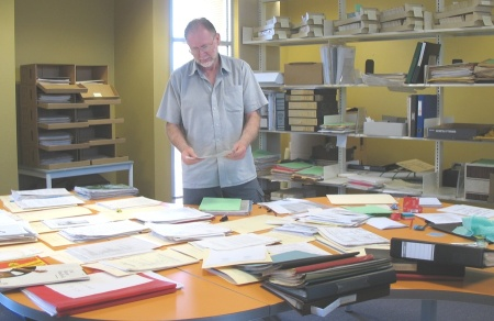 Sorting the unsorted (shelves at right) into folders and then into archive boxes (rear, left). {CHART photo]